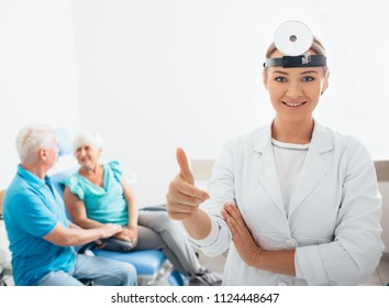 smiling ENT doctor with her senior patients in the background, focus on foreground at medical room