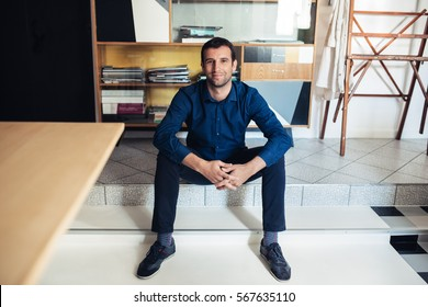 Smiling entrepreneur sitting in a large work studio