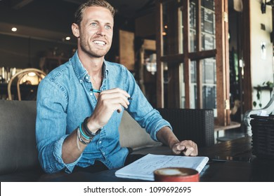 Smiling entrepreneur working on business project in city cafe