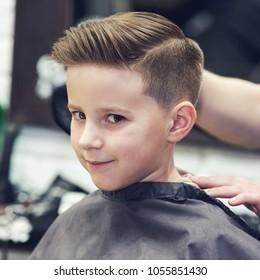 Smiling European boy in a barber shop. Ready look.