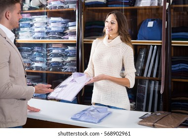 smiling european female shopping assistant offering various shirts in menâ??s cloths store
