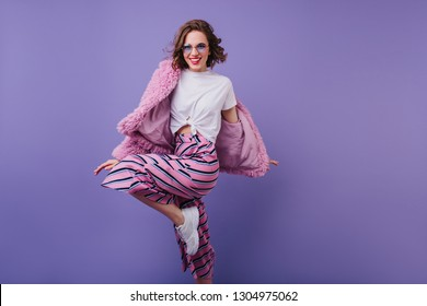 Smiling european lady in trendy sunglasses dancing in fur jacket. Studio shot of beautiful female model with wavy brown hair jumping during photoshoot.