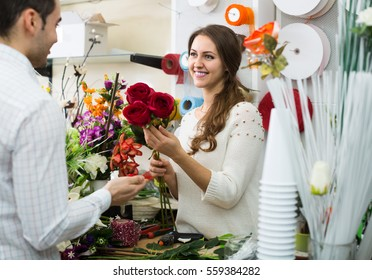 smiling european woman seller offering flowers man