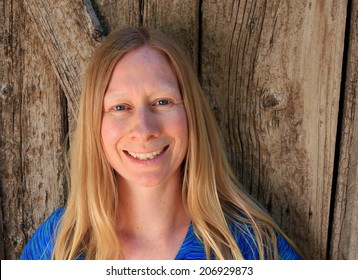 Smiling everyday woman with a barn wood background.