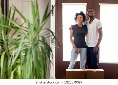 Smiling excited African American couple standing in hall with cardboard boxes with belongings, black man and woman embracing, moving day concept, feeling happy about buying new house