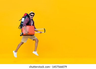 Smiling excited handsome Indian tourist man with backpack holding baggage and jumping ready to go for travel isolated on yellow background with copy space