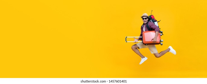 Smiling excited handsome Indian tourist man with backpack holding baggage and jumping ready to go for travel isolated on yellow banner background with copy space