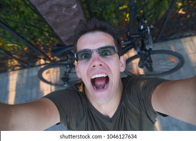 Smiling excited man in green shirt with sunglasses with bike bellow on green background of bushes and black metal fence stands with raised hands out of the frame.