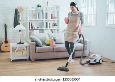 Smiling excited young housewife havig fun while cleaning floor with vacuum cleaner. Happy woman doing housework at home enjoy music wearing earphones. asian lady in arpon singing dancing house chores