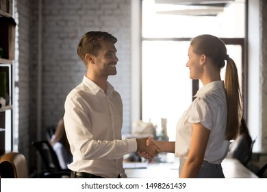 Smiling executive manager handshaking, greeting new hired employee in office, friendly businessman shaking hand of businesswoman, getting acquaintance, introduction, first impression at work