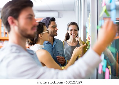 Smiling executives writing on sticky notes on glass wall in office