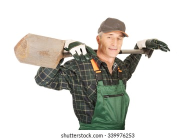 Smiling experienced gardener with a spade on shoulders