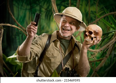 Smiling explorer taking a self portait with a skull in the jungle.