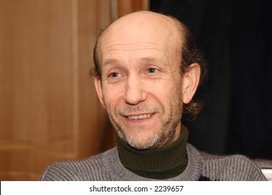 Smiling face of elderly man in grey jacket