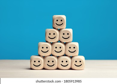 Smiling face icons on wooden cubes. Business service rating, customer satisfaction or teamwork concept.