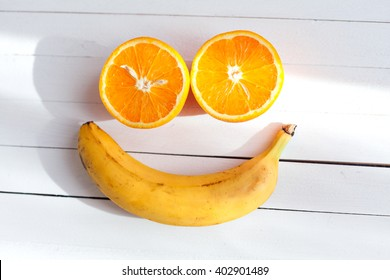 Smiling face made from fruit on a wooden background. Fruit smile. Two halves of oranges, and one banana. Vitamins for a good mood