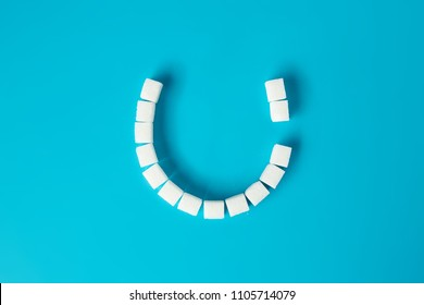 Smiling face with tooth decay made of sugar cubes on blue background. Sugar is the cause of tooth decay. concept.