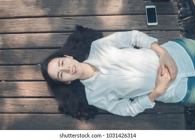 Smiling face Young asian woman in white shirt, blue jean sleeping on wood floor and blank screen on smart phone, tablet, cellphone. concept of asian woman lifestyle. view form top woman.