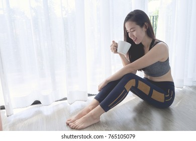 smiling face of young asian woman holding coffee cup on white curtain windows texture background with day light at living room. concept of asian woman health care.