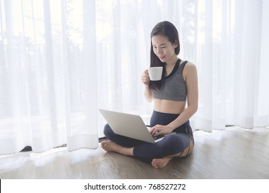 Smiling face young asian woman in sport bra sitting in living room on white curtain window texture background, hold coffee cup, drinking coffee and using laptop. concept of asian lifestyle.