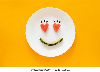 Smiling faces on a white plate on an orange background. Heart shape from watermelon. Smiling symbol. Concept enjoy eating. Summer time