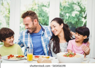 Smiling family with arm around while sitting at dining table with food in home