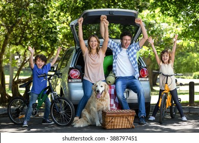 Smiling family with arms up in front of a car