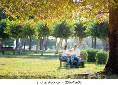 Smiling family in autumn park. Happy young parents with little kid sitting on the bench under the tree.