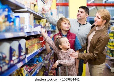 Smiling family with children choosing cereal for breakfast in supermarket. Focus on girl