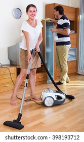 Smiling family couple vacuuming clean-up in living room