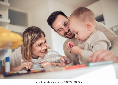 Smiling family drawing together in kitchen at home.