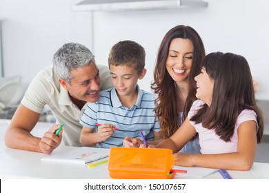 Smiling family drawing together in kitchen at home