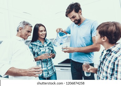 Smiling Family Drinking Water in Glasses at Home. Father and Son. Smiling People. Parenthood Concept. Family at Home. Happy Family. Glass of Water. Young Woman. Family in Dining Room.