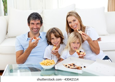 Smiling family eating a pizza sitting on the floor in the living-room