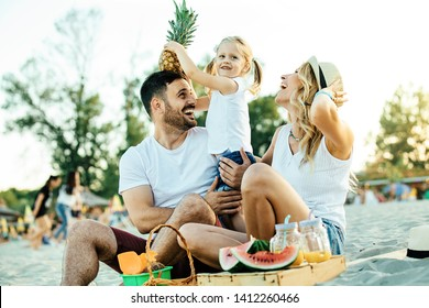 Smiling family enjoying beach and having picnic.