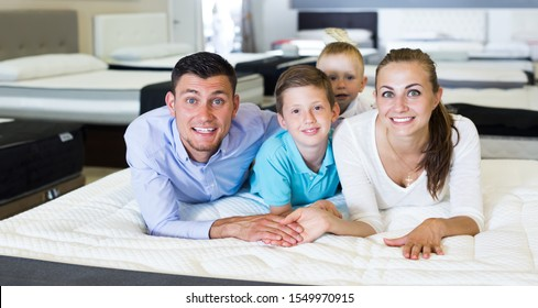 Smiling family of four choosing right mattress in modern home furnishings shop