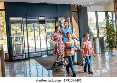 Smiling family of four enters to the hotel lobby to check in at the reception for vacation.