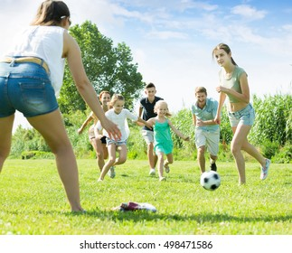 Smiling family with four kids playfully running after ball outdoors on green lawn in park. Focus on teenager girl