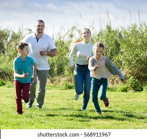 Smiling family of four people happily playing and running together outdoors