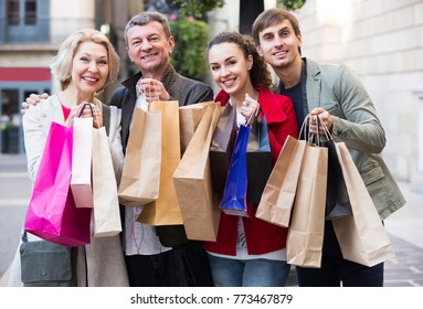Smiling family of four with shopping bags on city street