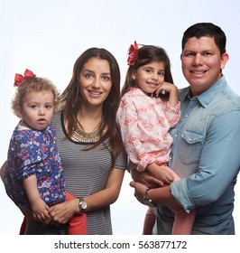 Smiling family of four with two daughters isolated on white background