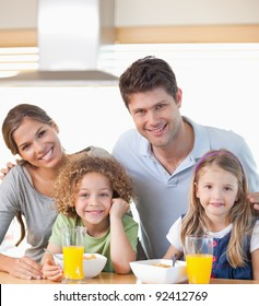 Smiling family having breakfast in their kitchen