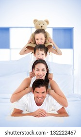 Smiling family leaning on each others shoulders in bed with blue grid design on wall