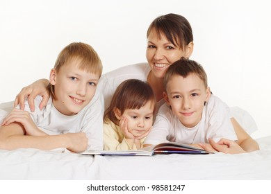 smiling family lie on the floor and reading
