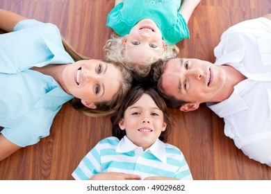 Smiling family lying in circle on the floor at home