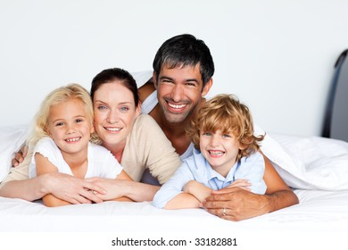 Smiling family lying together on bed