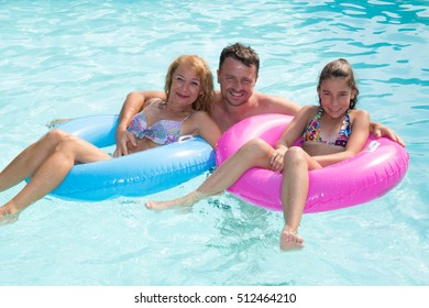 Smiling family on the pool having fun together
