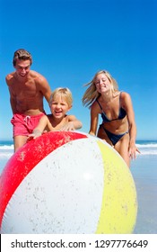 Smiling family on summer vacation playing with ball together at beach