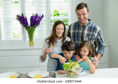 Smiling family preparing bowl of salad in kitchen at home