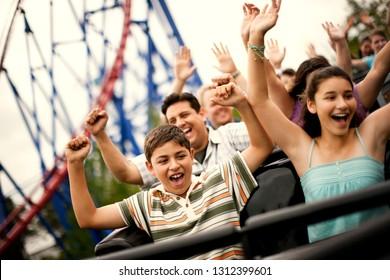 Lächelnde Familie reiten auf einer Achterbahn in einem Vergnügungspark.